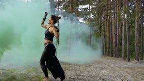 A mulher está dançando a dança tribal na coluna do fumo azul filme