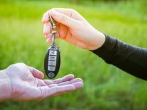 A mulher está dando a chave do carro ao homem Imagens de Stock Royalty Free