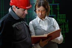 A mulher está dando instruções ao trabalhador com o capacete vermelho no poder imagens de stock royalty free