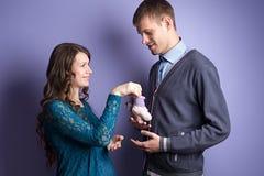 A mulher está dando os sapatinhos de lã do bebê futuro a seu homem foto de stock royalty free