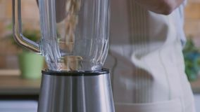 A mulher está derramando o amendoim no misturador, vídeo de movimento lento video estoque