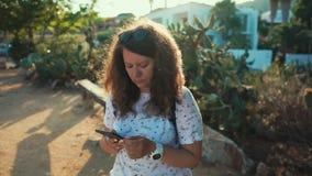 A mulher está descansando em um banco no dia ensolarado quente, surfando o Internet pelo smartphone vídeos de arquivo