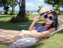 A mulher está descansando na rede imagens de stock royalty free
