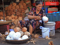 A mulher está descascando cocos no mercado de rua na matiz, Vietname Fotos de Stock