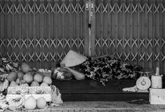 A mulher está dormindo em sua tenda dos alimentos frescos em uma rua em Ho Chi Minh City, Vietname imagem de stock