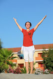 A mulher está e levanta contente as mãos acima Fotos de Stock Royalty Free