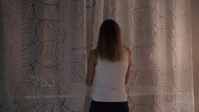 A mulher está em Windows na noite que olha luzes de rua, cortinas filme