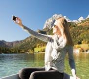 A mulher está enfileirando com um barco de enfileiramento com um lago nas montanhas fotografia de stock
