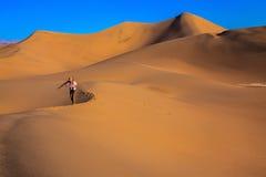 A mulher está entre dunas de areia Fotos de Stock Royalty Free