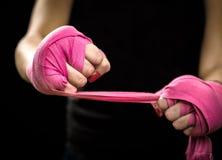 A mulher está envolvendo as mãos com os envoltórios cor-de-rosa do encaixotamento Fotografia de Stock Royalty Free