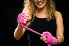 A mulher está envolvendo as mãos com os envoltórios cor-de-rosa do encaixotamento Fotos de Stock Royalty Free