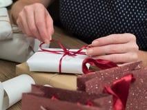 A mulher está envolvendo presentes do Natal Imagem de Stock