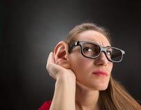 A mulher está escutando fotos de stock