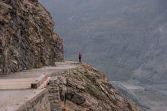 A mulher está estando na borda das montanhas rochosas Foto de Stock Royalty Free