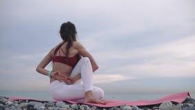 A mulher está executando a torção do corpo que senta-se no seacoast, na prática da ioga e em ginástico vídeos de arquivo