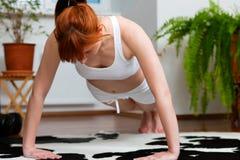 A mulher está exercitando em casa Fotografia de Stock