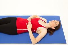 A mulher está exercitando em uma esteira Imagens de Stock