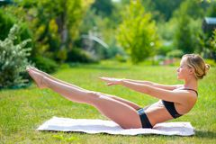 A mulher está exercitando na grama verde durante o nascer do sol do verão fotos de stock royalty free