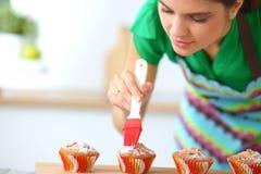 A mulher está fazendo bolos na cozinha Imagem de Stock