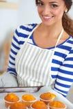 A mulher está fazendo bolos na cozinha Imagens de Stock