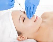 A mulher está fazendo injeções da cirurgia estética Foto de Stock