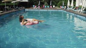 A mulher está flutuando com um círculo inflável da filhós na associação swomming video estoque
