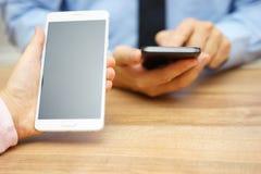 A mulher está guardando o telefone celular esperto grande com a tela emtpy com b Fotografia de Stock