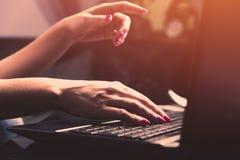 A mulher está guardando um telefone em uma mão, a outro está apontando em um portátil imagem de stock