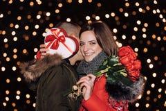 A mulher está guardando uma caixa de presente e rosas e está sorrindo ao abraçar o homem fotografia de stock