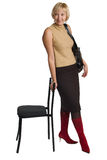 A mulher está, inclinando-se sobre uma cadeira. Imagem de Stock Royalty Free