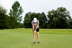 A mulher está jogando o golfe no verão do curso foto de stock