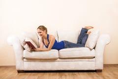 A mulher está lendo em uma sala de estar fotografia de stock royalty free