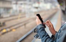 A mulher está lendo a mensagem de texto no telefone celular fotos de stock royalty free