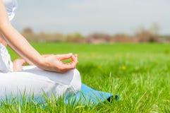 A mulher está meditando o assento na pose de Lotus na grama no parque imagens de stock