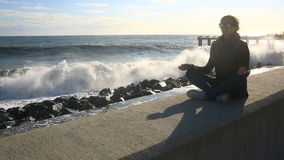 A mulher está meditando sobre a praia durante uma tempestade Equanimidade, resistência ao esforço video estoque