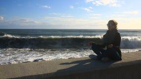 A mulher está meditando sobre a praia durante uma tempestade Equanimidade, resistência ao esforço filme