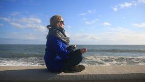 A mulher está meditando sobre a praia durante uma tempestade Equanimidade, resistência ao esforço vídeos de arquivo