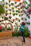 A mulher está molhando as flores na parede, Fest do pátio de Córdova, termas imagem de stock