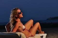 A mulher está na praia da noite foto de stock