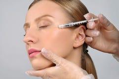 A mulher está obtendo a injeção do botox Tratamento antienvelhecimento e cara foto de stock