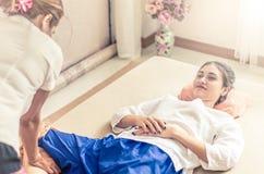 A mulher está obtendo a massagem do pé nos termas ao encontrar-se em uma cama dos termas Foto de Stock