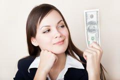 A mulher está olhando 100 dólares de nota de banco Imagens de Stock Royalty Free