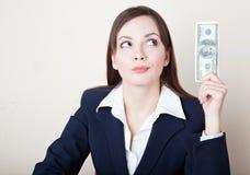 A mulher está olhando 100 dólares de nota de banco Fotografia de Stock Royalty Free
