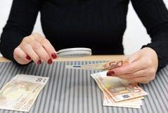 A mulher está olhando através de uma lupa para a moeda falsa imagem de stock