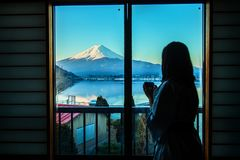 A mulher está olhando o moutain de Fuji fora da janela ao guardar um copo do chá na manhã Foto de Stock Royalty Free