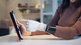 A mulher está operando uma tabuleta com sua mão protética filme