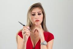 A mulher está pensando sobre o que escrever cleavage Pessoa loura a foto de stock royalty free