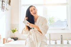 A mulher está penteando o cabelo imagens de stock