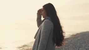 A mulher está perto do mar, senhora com cabelo longo aprecia o cenário natural bonito filme