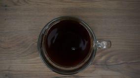 A mulher está pondo o açúcar na xícara de café filme